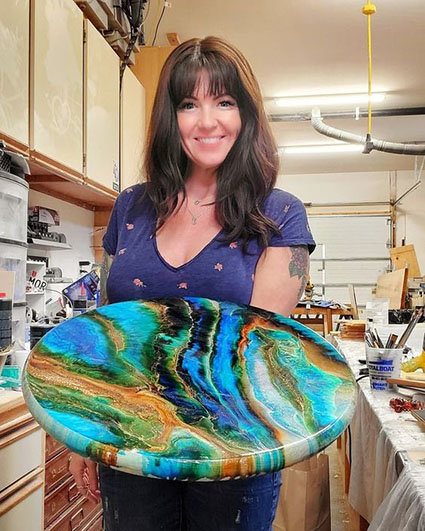 Resin artist and teacher Jess Crow, of Crow Creek Designs, shows off a resin-pouring table project.